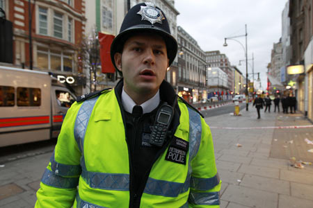Police maintain a security cordon following a fatal stabbing on Oxford Street in London December 26, 2011.  A male was pronounced dead at the scene and a number of arrests had been made, police said.