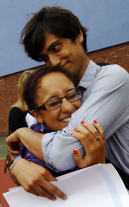 Head boy Mathew Chandy (R) celebrates his 4 A grades with Lilia Kazem who earned an A*, A, B result on their A level college entrance exams at the Harris Academy in Crystal Palace in south London August 18, 2011. Sixth-form students face a scramble for university places in the final year before tuition fees rise after another record set of A-level results.