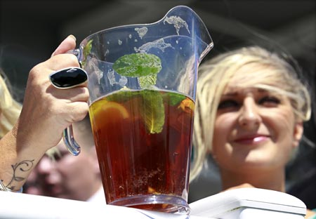 Women drink a traditional Pimm's Cup cocktail as they wait for the start of the second race during Ladies Day at Epsom Racecourse in southern England June 3, 2011.