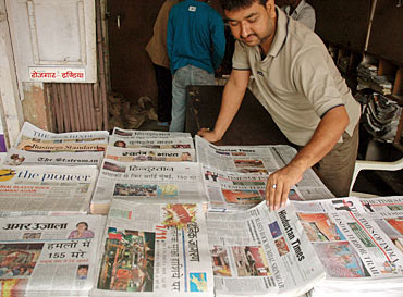 A vendor arranges Indian newspapers that carry reports and pictures of the Mumbai blasts in the northern Indian city of Allahabad July 12, 2006
