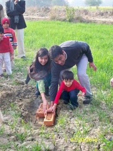 Pooja, Shashank and their son laying the foundation stone for the school building