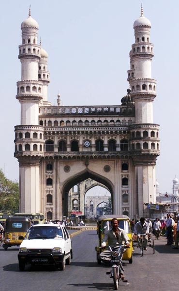 Residents of Hyderabad drive past the Charminar, the city's best known monument