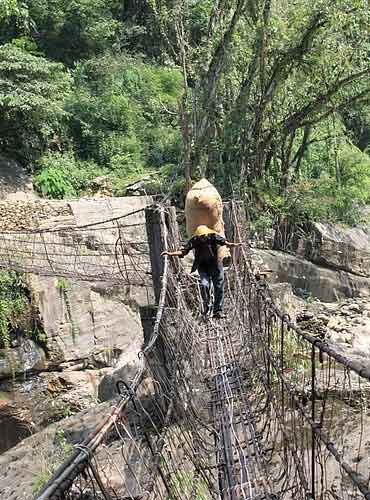 The narrow iron suspension footbridge.