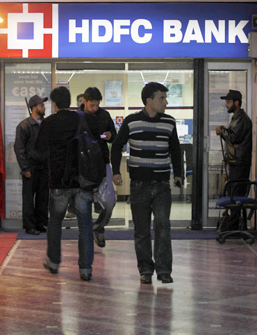 People walk in and out of a HDFC bank branch in Srinagar
