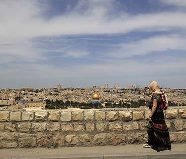 A woman takes a photograph from the Mount of Olives of the Dome of the Rock in Jerusalem's Old City.