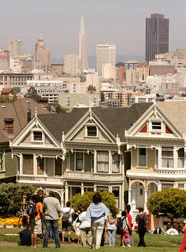 Visitors look at the skyline of San Francisco, including Victorian homes known as the Painted Ladies, in San Francisco, California