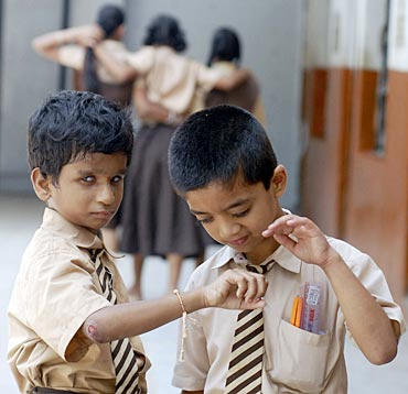 Visually impaired schoolboys play with a sacred thread known as Rakhi tied onto the wrist of one of the boys inside their school in the southern Indian city of Hyderabad
