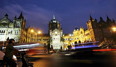 A scooterist stops in front of Chhatrapati Shivaji Terminus railway station