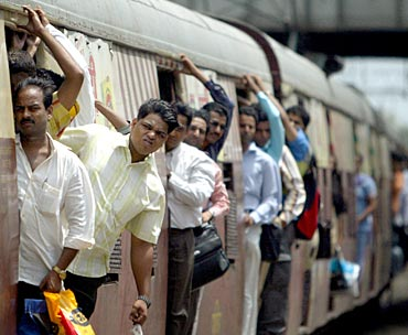 Commuters lean out of a train in Mumbai