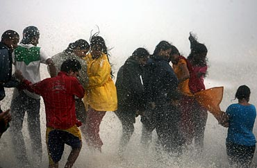 People get drenched by a large wave during high tide at Mumbai's seafront