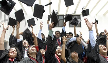 Students of the graduating class of the National Academy of Legal Studies and Research (NALSAR), University of Law, throw their caps in the air as they participate in their farewell cheer in the southern India