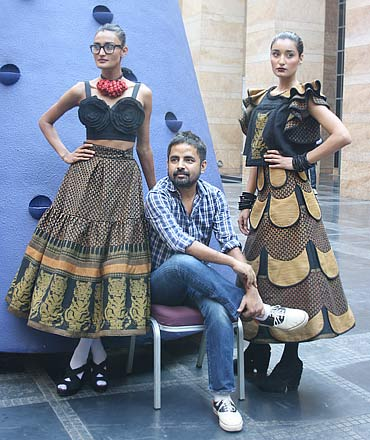 bcd3d7ddd00 Sabyasachi Mukherjee with two of his creations poses for the shutterbugs.  Sabya is scheduled to