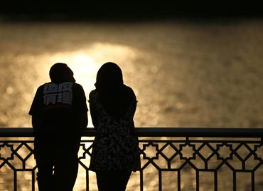 A couple watch a sunset near a lake in Putrajaya, Malaysia