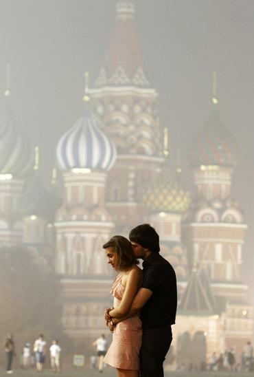 A couple stands in front of St. Basil's Cathedral shrouded in smog in Moscow