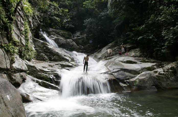 A man stands at Lopo Waterfall in Hulu Langat near Kuala Lumpur