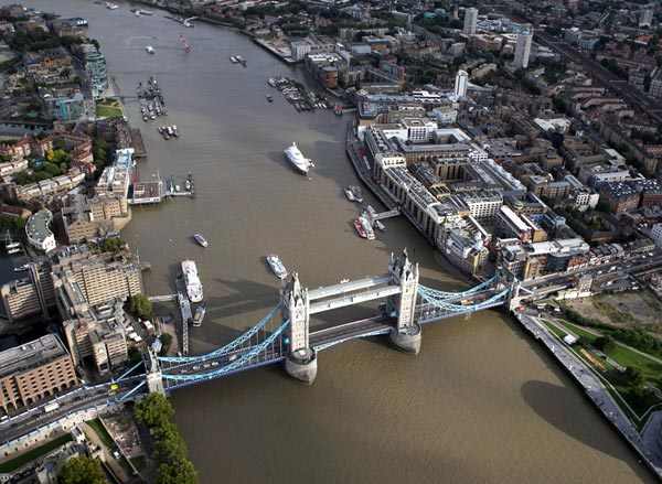 An aerial view of the Thames river in London from the air with Tower Bridge in the foreground in London, England