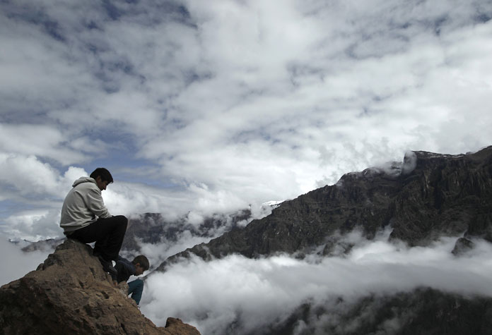 eople sit at an observation point, as they waits to see condors, in the Colca canyon at the Colca valley in Arequipa, south of Lima.