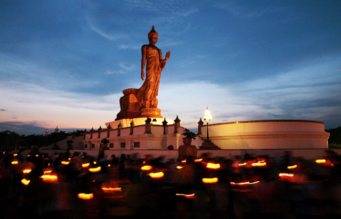 People walk around the Buddha statue at sunset holding candles for prayers at Buddhist Park on Visakha Puja Day in Nakhon Pathom