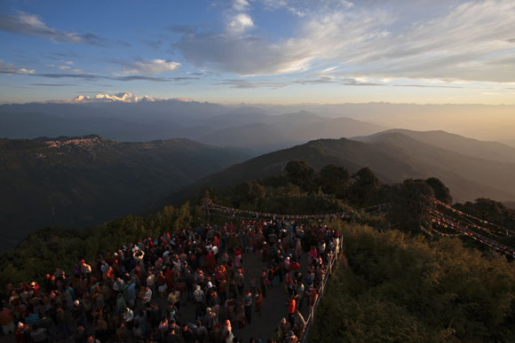 Visitors watch the sun rise from Tiger Hill near Darjeeling (C) in the Indian state of West Bengal October 2, 2009. Also pictured is Khangchendzonga (top) also spelled Kanchenjunga, which means 'The Five Treasures of Snows', is the third highest mountain in the world with an altitude of 8,586 metres (28,169 feet).