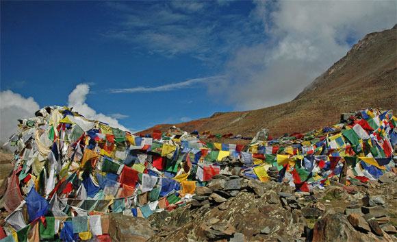 Tibetan Budhist prayer flags in five colours flutter in the wind near Barlacha La pass along the Manali Leh Highway