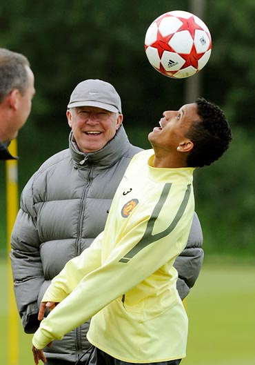 Manchester United's Nani (R) heads the ball watched by coach Alex Ferguson during a practice session at the club's Carrington training ground in Manchester, northern England