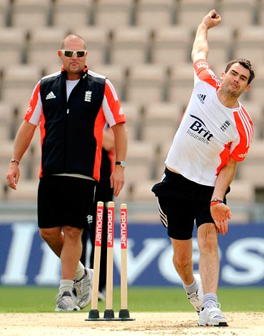 England's James Anderson bowls watched by bowling coach David Saker (L) during a training session