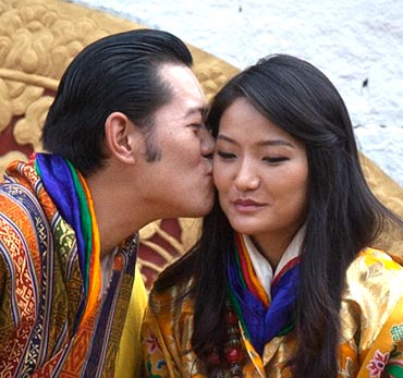 King Jigme Khesar Namgyel Wangchuck (L) kisses Queen Jetsun Pema in front of thousands of residents gathered for the third day of their wedding ceremony at the Changlimithang stadium in Bhutan's capital Thimphu on October 15, 2011