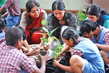 Two young women from iVolunteer engage students in planting saplings