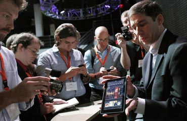 Reporters crowd around the new Kindle Fire at a news conference during the launch of Amazon's new tablets in New York, September 28, 2011.