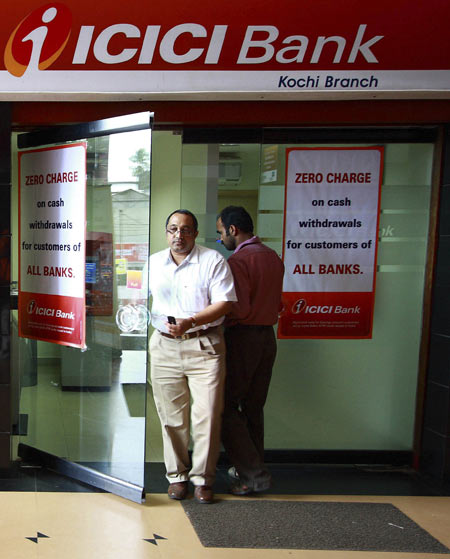 A man leaves an automated teller machine (ATM) facility of ICICI bank in the southern Indian city of Kochi August 6, 2009.