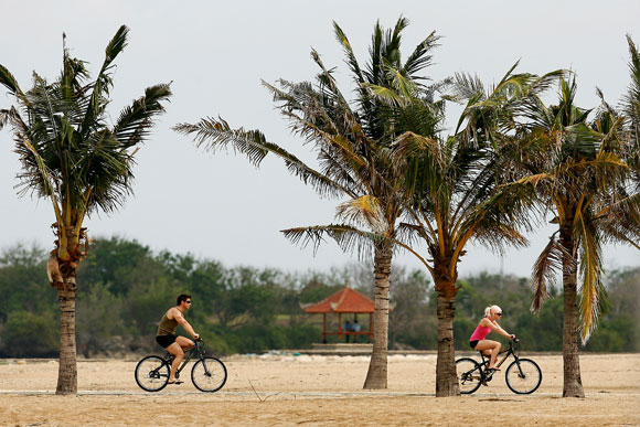 Tourists ride along Nusa Dua Beach