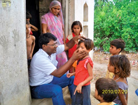 Dr Bali examinining a child in the slums