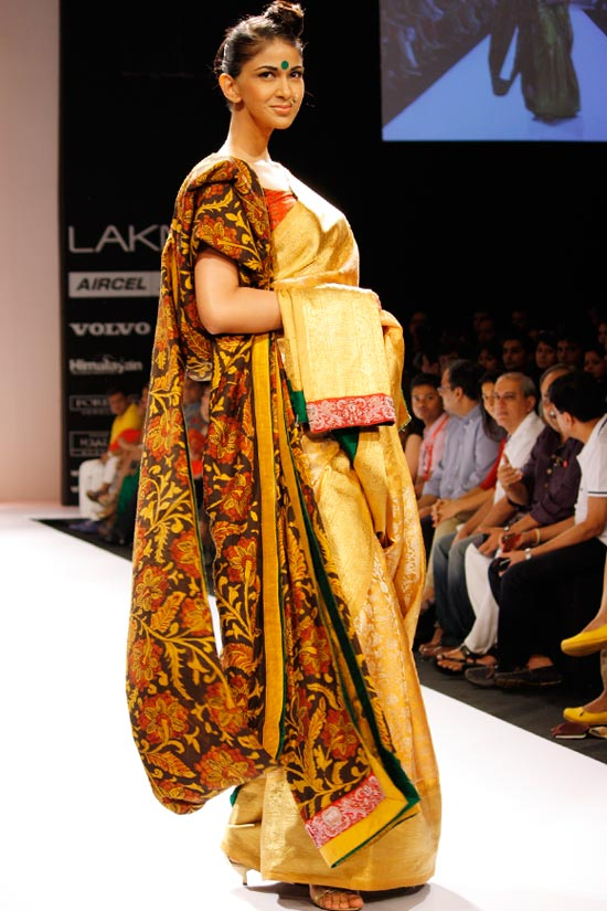 We see a lovely golden sari sporting a red border, with more draping added on courtesy an earthy floral shawl.