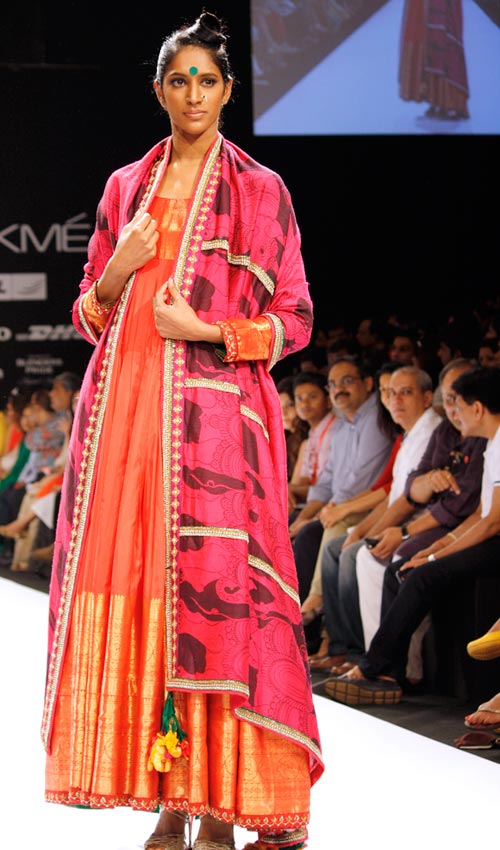 A delightful orange anarkali cascades to the floor and is set off by a pink and black dupatta.