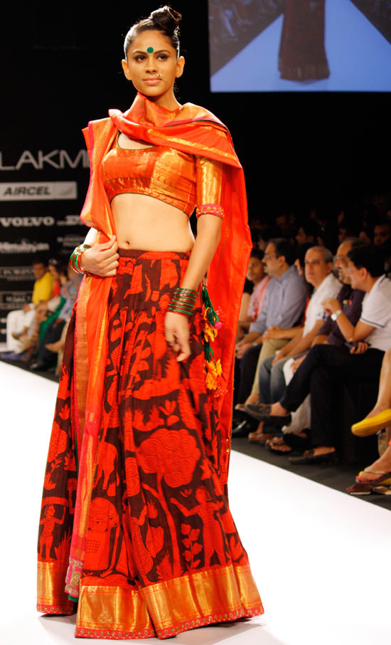 We see a lovely blend of Kanjeevaram and kalamkari once more, in sheen-tinted orange and, red and black.