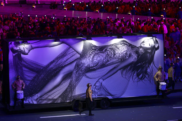 A billboard featuring the image of model Naomi Campbell is displayed at the start of the fashion show