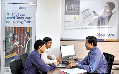 A Federal Bank officer counsels customers at New Delhi's Nehru Place branch