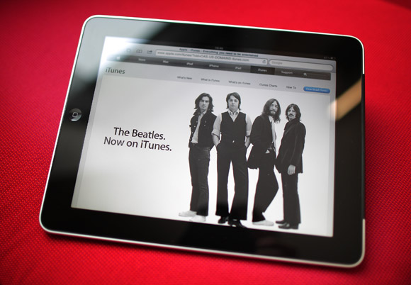 An Apple iPad tablet displays a web page from the iTunes store