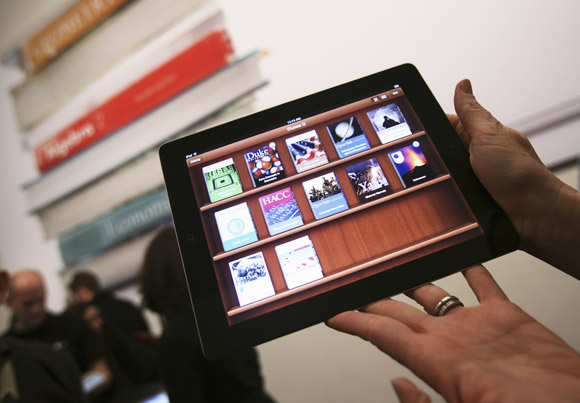 A woman holds up an iPad with the iTunes U app after a news conference introducing a digital textbook service in New York January 19, 2012