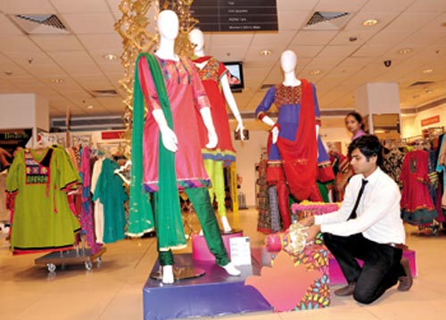 A visual merchandiser adds the finishing touches to a display at Shoppers Stop at MGF - Metropolitan Mall, New Delhi