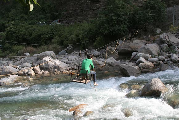 You have to cross the Tirthan river in a makeshift cable car to reach Raju's homestay.