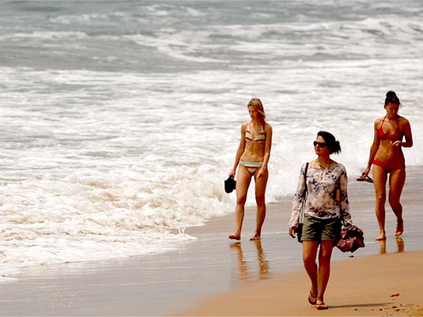 Tourists walk on the Anjuna beach in Goa