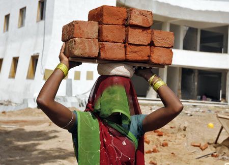 A labourer carries bricks at a residential complex under construction on the outskirts of Ahmedabad.