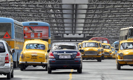 Traffic moves across Howrah Bridge in Kolkata April 8, 2011. Higher input costs and interest rates are seen crimping demand for cars in India, the second-fastest growing auto market in the world after China, with sales growth expected to more than halve in this fiscal year to 12-15 percent from the peaks scaled a year earlier.