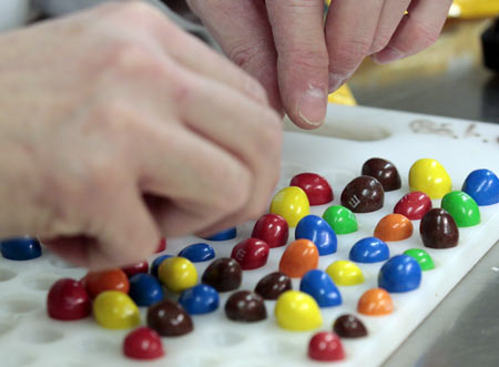 An employee checks samples of M&M's candies at the production line of candy and chocolate maker Mars Chocolate France's plant in Haguenau, eastern France, December 13, 2011. Mars will invest 45 million euros ($59 million) during the next 18 months in its Haguenau plant to increase the production of M&M's candies by 20 percent.
