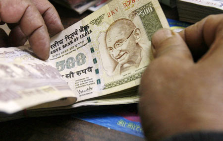 An employee counts Indian rupee notes at a cash counter inside a bank in Agartala, capital of India's northeastern state of Tripura December 31, 2010. India's fiscal deficit from April to November was 1.86 trillion rupees ($41.6 billion), or 48.9 percent of the full-year target, the government said in a statement on Friday.