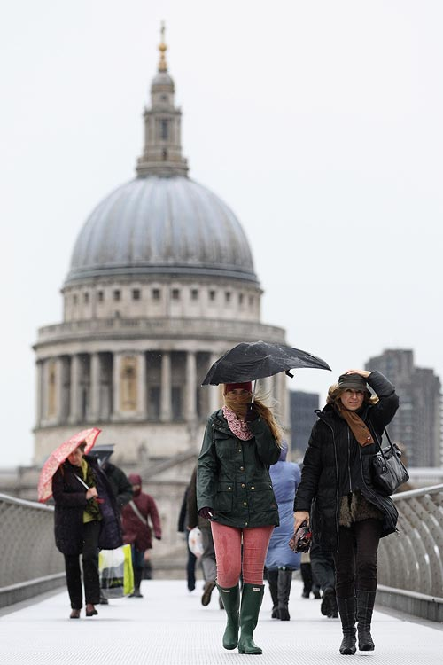 People walk over the Millenium Bridge in the pouring rain in London, United Kingdom