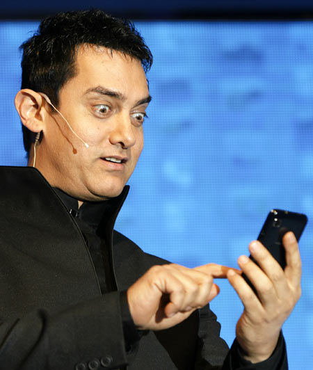 Bollywood actor Aamir Khan reacts as he holds a mobile phone during a promotional event of a mobile company in New Delhi June 16, 2010.