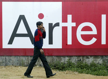 A boy talks on a mobile phone as he walks past a billboard of Bharti Airtel