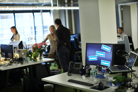 Facebook workers stand at their desks before a news conference at their office in New York December 2, 2011.